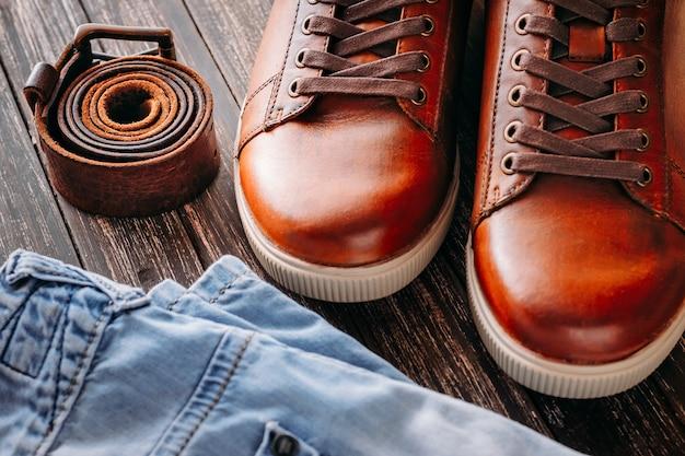 Gros plan des bottes pour hommes en cuir marron et blue jeans sur fond en bois foncé Photo Premium
