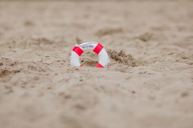 Gros plan d'une bouée de sauvetage miniature creuser dans le sable à la plage Photo Premium