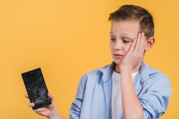 Gros plan, bouleversé, garçon, regarder, cassé, écran, de, téléphone portable, sur, jaune, fond Photo gratuit