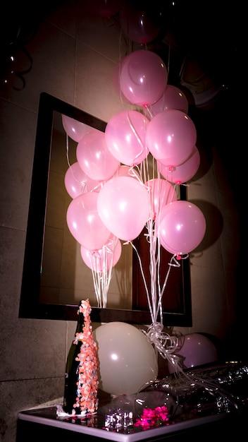Gros plan, de, bouteille champagne, à, ballons roses, sur, bureau Photo gratuit
