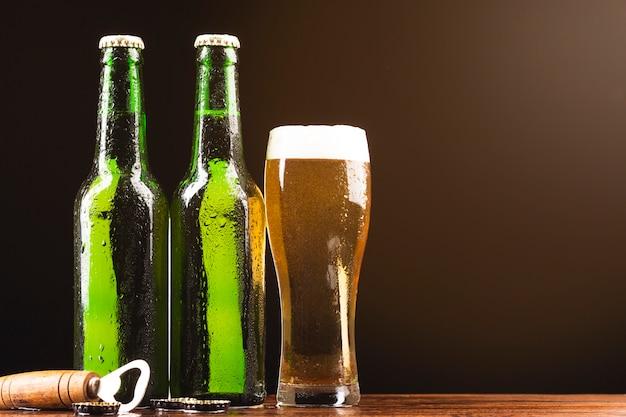 Gros plan de bouteilles de bière avec un verre Photo gratuit