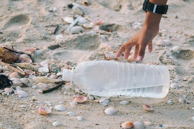 Gros plan sur les bras les enfants ramassent des bouteilles en plastique laissées sur la plage. Photo Premium