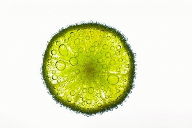 Gros Plan De Bulles D'air Couvrant Une Tranche De Citron Vert Citronnée Flottant Dans L'eau Photo gratuit