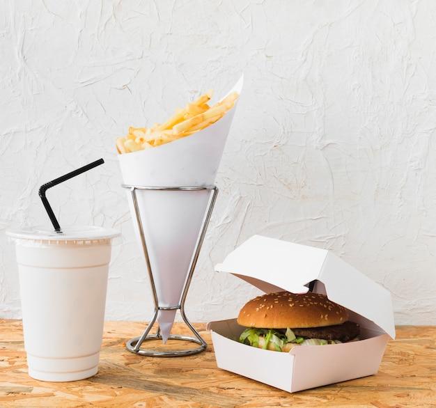 Gros plan de burger; pommes frites et coupe sur un bureau en bois Photo gratuit