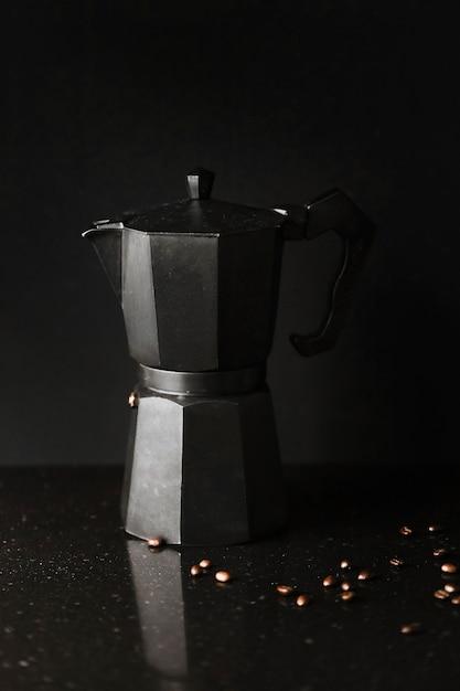 Gros plan d'une cafetière avec des grains de café torréfiés sur fond noir Photo gratuit