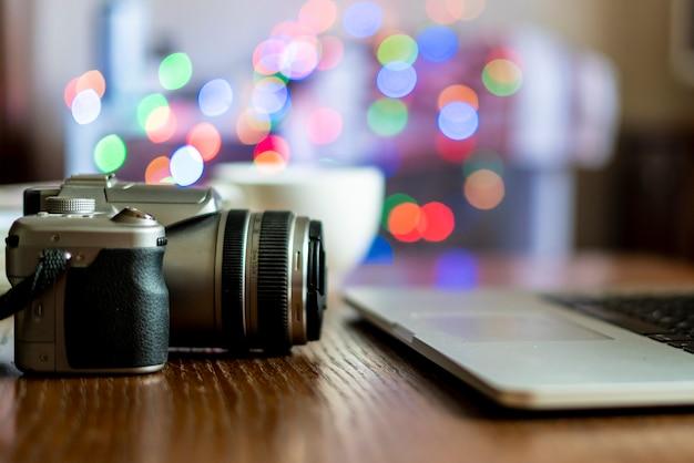 Gros plan de caméra sur la table du lieu de travail du photographe avec un ordinateur portable Photo Premium