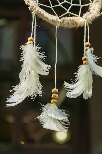 Gros plan d'un capteur de rêves avec des plumes blanches Photo Premium