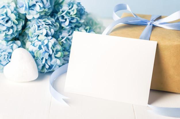 Gros Plan De La Carte De Voeux Blanche Vide Avec Boîte-cadeau De Recyclage Marron Et Fleurs D'hortensia Bleu Photo Premium