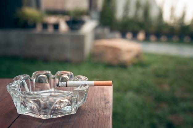 Gros plan de la cigarette sur le bord du cendrier sur la table en bois. Photo Premium