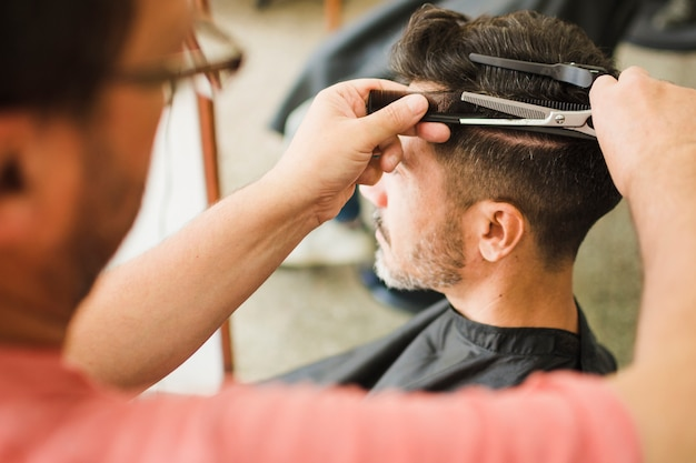 Gros plan d'un client se faire couper les cheveux par un coiffeur Photo gratuit