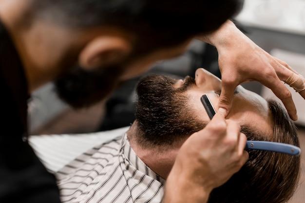 Gros plan, de, a, coiffeur, main, couper, cheveux homme, à, rasoir Photo gratuit
