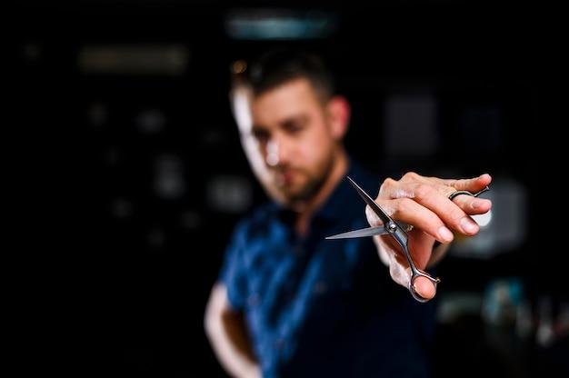 Gros plan coiffeur tenant des ciseaux Photo gratuit