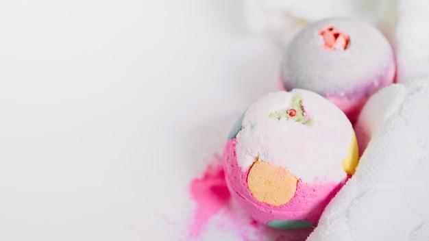 Gros plan, coloré, bombes bain, serviette, sur, blanc, toile de fond Photo gratuit