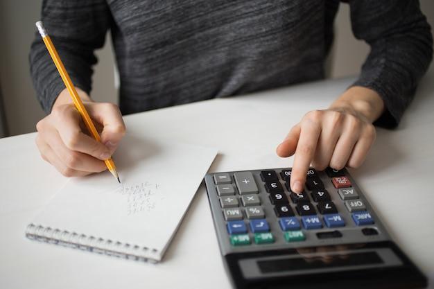 Gros plan de comptable utilisant la calculatrice et l'écriture Photo gratuit