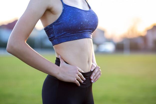 Gros plan d'un corps mince fille dans des vêtements de sport. ventre plat à la suite d'un entraînement physique. Photo Premium