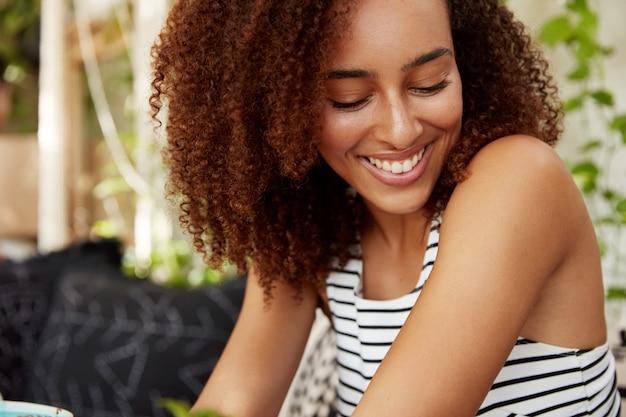 Gros Plan Sur Le Côté Portrait De L'heureuse Jeune Femme Afro-américaine Regarde Avec Une Expression Timide Vers Le Bas, Habillée Avec Désinvolture, Ravie De Passer Du Temps Libre Avec Son Petit Ami, Avoir Une Conversation Agréable Photo gratuit