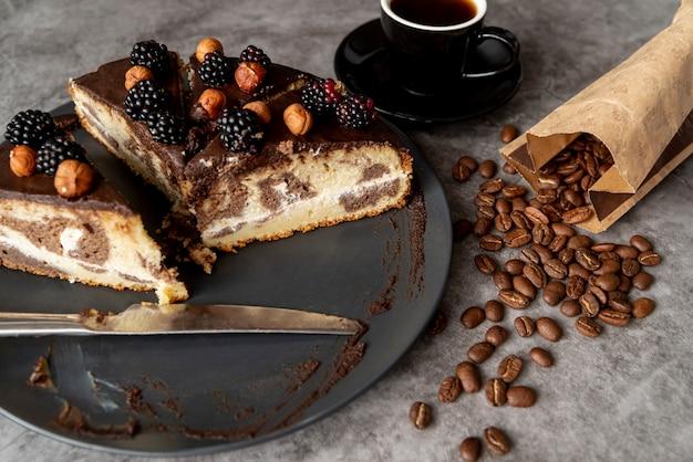 Gros plan couper le gâteau avec du café Photo gratuit