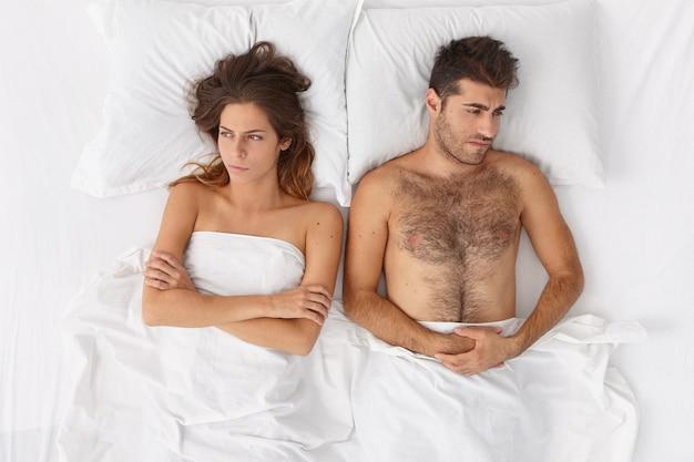 Gros Plan Sur Couple Allongé Dans Son Lit Sous Une Couverture Blanche Photo gratuit