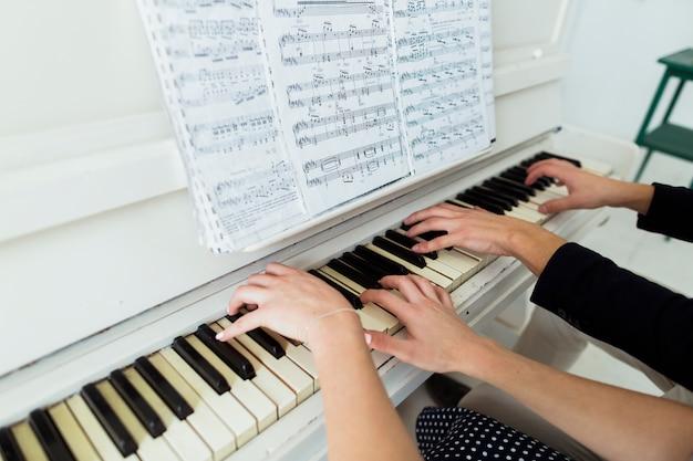 Gros plan, couple, main, piano jouant, feuille musicale Photo gratuit