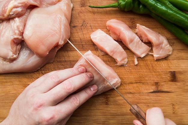 Gros plan, coupure, poulet cru, couteau, table, bois Photo gratuit