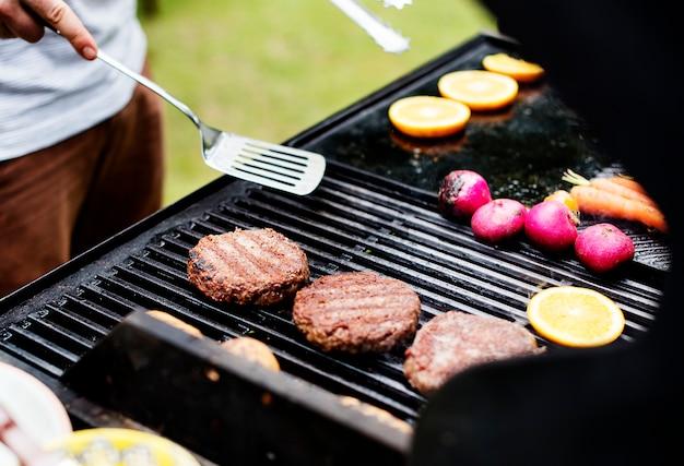 Gros plan de la cuisson des galettes de hamburger sur le gril à charbon Photo gratuit