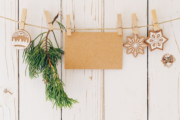Gros Plan De Décoration De Noël Et Carte De Papier Vierge Accroché Sur Fond De Bois. Photo Premium