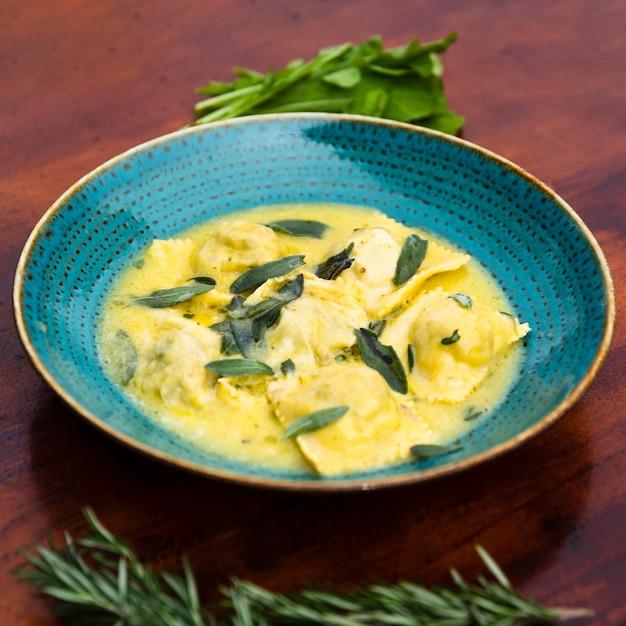 Gros plan, délicieux, pâtes ravioli, garnir, à, feuille basilic, sur, table en bois Photo gratuit