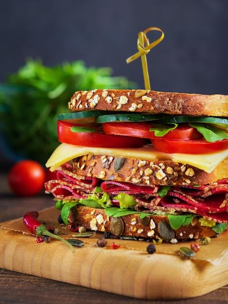 Gros plan d'un délicieux sandwich au salami, au fromage et aux légumes frais. Photo Premium