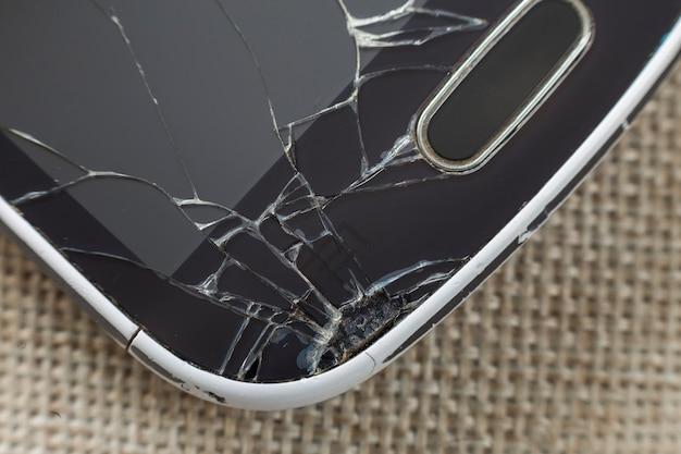 Gros Plan Détail Du Vieux Téléphone Portable Noir Avec écran Fissuré Sur Fond De Tissu Clair. Concept De Réparation Et D'entretien De Gadgets. Photo Premium