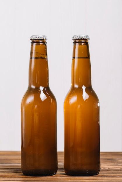 Gros plan, de, deux, bière, bouteilles, sur, bois, surface Photo gratuit