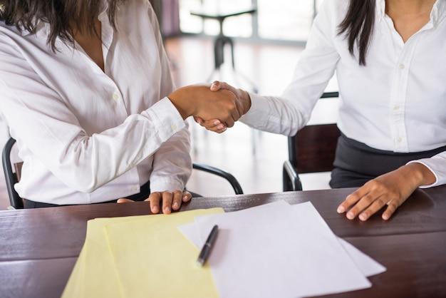 Gros plan de deux femmes d'affaires se serrant la main et assis au bureau. Photo gratuit