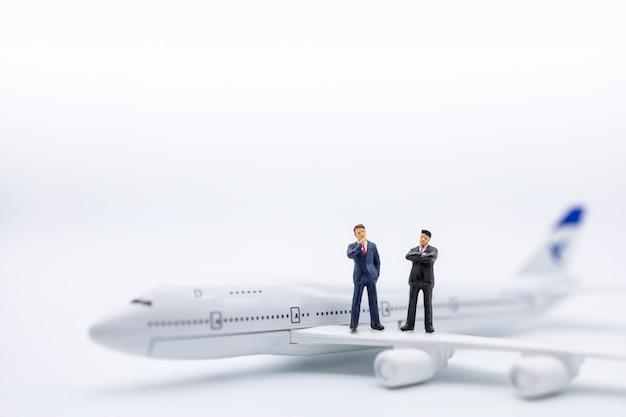 Gros plan de deux figurine miniature de l'homme d'affaires, debout sur l'aile de l'avion sur blanc. Photo Premium