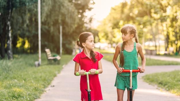 Gros plan, deux, filles, équitation, coup, scooter, regarder, autre, dans parc Photo gratuit