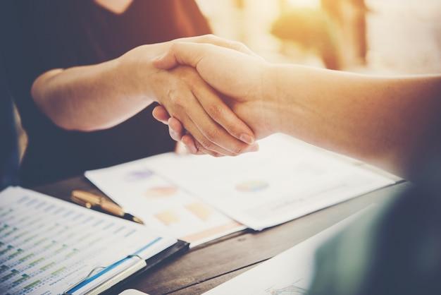 Gros plan de deux hommes d'affaires serrant la main pendant que vous vous asseyez sur le lieu de travail. Photo gratuit