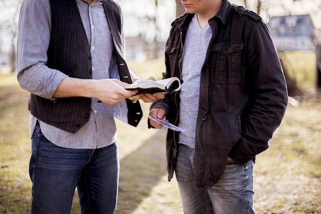 Gros Plan De Deux Hommes Debout Près L'un De L'autre Et Lisant La Bible Photo gratuit
