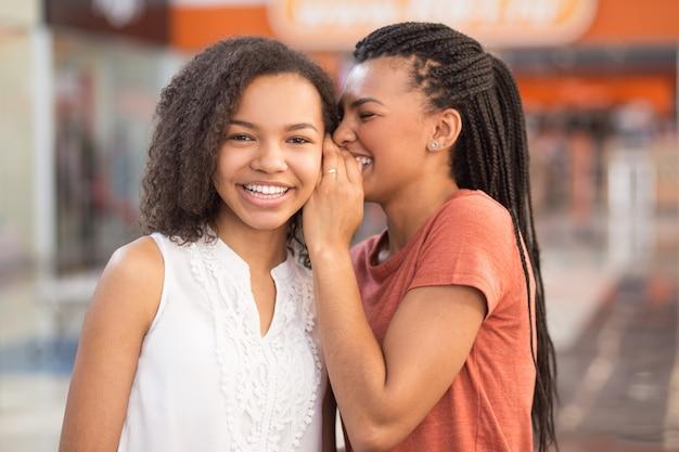 Gros plan de deux jolies noires partageant des secrets Photo gratuit
