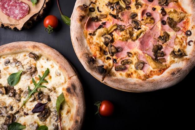 Gros plan, deux, pizza italienne, à, différent, garnitures, et, tomate cerise Photo gratuit