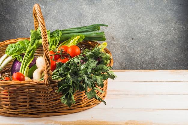 Gros plan de divers légumes frais dans un panier en osier sur fond en bois Photo gratuit