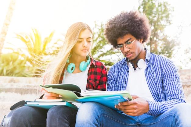 Gros plan, diversifié, jeune, masculin, et, étudiante, lecture livre Photo gratuit
