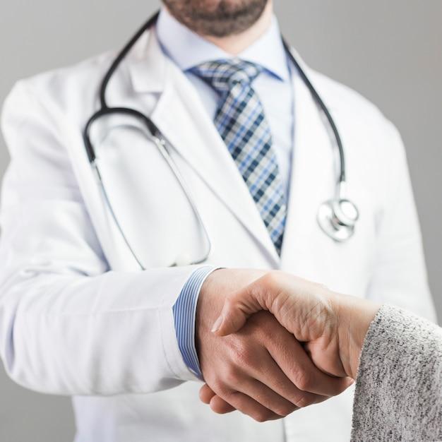 Gros plan, docteur, serrer main, patient, contre, fond gris Photo gratuit