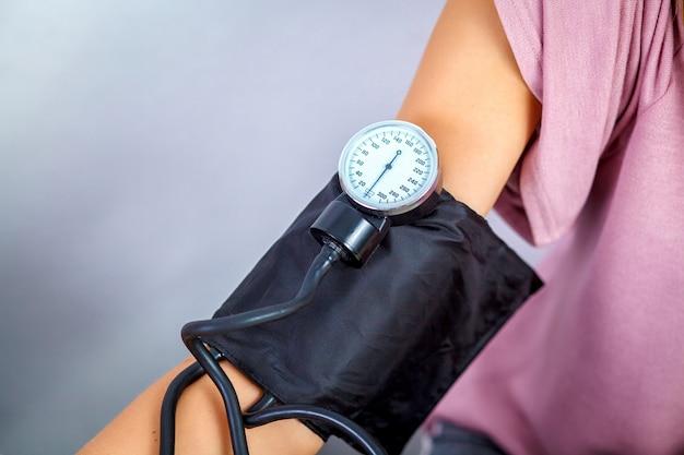 Gros plan d'un docteur vérifiant la pression artérielle d'un patient. concept de service médical. Photo Premium