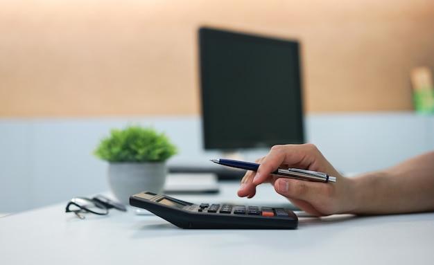 Gros plan sur le doigt de l'employé homme appuyez sur la calculatrice pour gérer le concept des dépenses Photo Premium