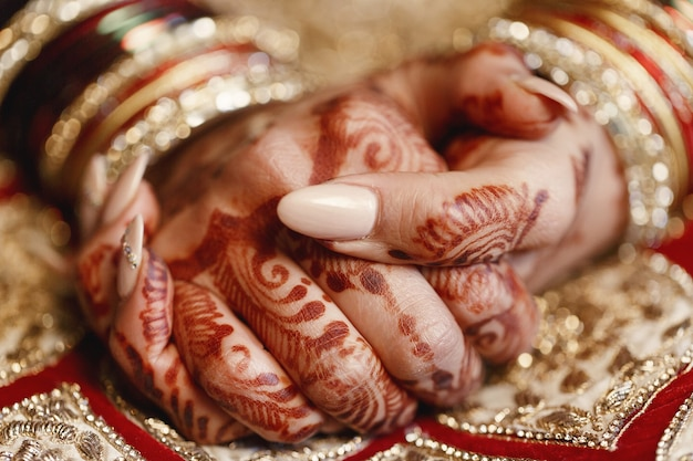 Gros plan des doigts de la longue mariée recouvert de mehndi et couché Photo gratuit