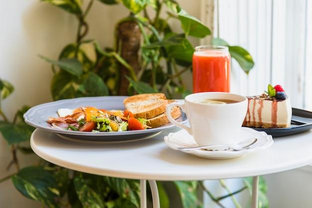 Gros plan du café; petit déjeuner; gâteau au fromage et smoothie rouge sur une table blanche Photo gratuit
