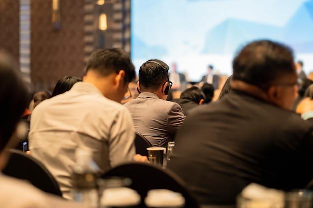 Gros plan du casque d'interprétation de la vue arrière du public qui porte et écoute Photo Premium