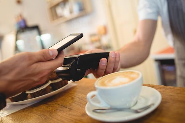 Gros Plan Du Client Avec Téléphone Portable Et Barista Avec Lecteur De Carte Photo Premium