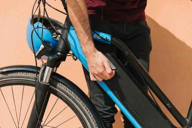 Gros Plan Du Cycliste Attachant La Batterie Du Vélo électrique Photo gratuit