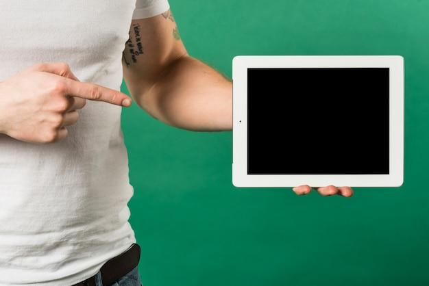 Gros plan du doigt de l'homme pointant vers la tablette numérique avec affichage à l'écran noir Photo gratuit