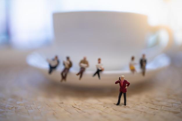 Gros plan du groupe de l'homme d'affaires miniature figure debout et faire un appel téléphonique avec une tasse blanche de café. Photo Premium