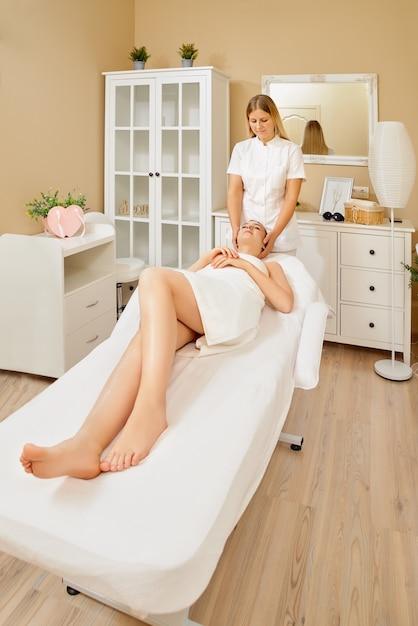 Gros Plan Du Jeune Masseur Féminin Faisant Un Massage Sur Le Visage Pour Jeune Jolie Cliente Dans Le Salon Spa Photo Premium